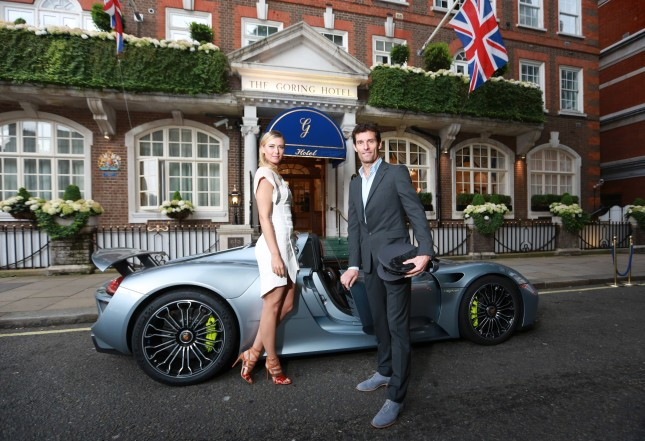 French Open winner, Maria Sharapova, is picked up from The Goring hotel in Central London by Porsche Works Driver and 'world's fastest chauffeur' Mark Webber, in the plug-in hybrid Porsche 918 Spyder and driven to the Women's Tennis Association (WTA) Pre-Wimbledon Party at the Kensington Roof Gardens.  Photo. Picture date: Thursday June 19, 2014. Hitting 0-60 mph in 2.5 seconds and with a top speed of 214 mph, the 918 Spyder is the most powerful road car Porsche has built to date, yet is exempt from the Congestion Charge as the plug-in hybrid super sports car emits less CO2 than most small cars and many other hybrid vehicles. Photo credit  should read: Matt Alexander/PA Wire
