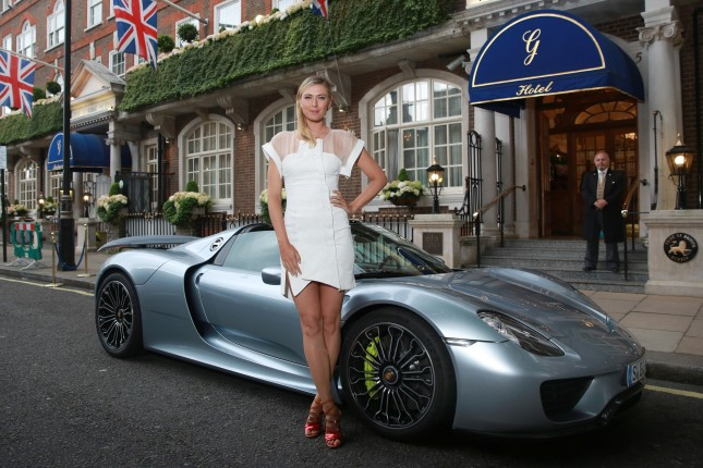 French Open winner, Maria Sharapova, is picked up from The Goring hotel in Central London by Porsche Works Driver and 'world's fastest chauffeur' Mark Webber, in the plug-in hybrid Porsche 918 Spyder and driven to the Women's Tennis Association (WTA) Pre-Wimbledon Party at the Kensington Roof Gardens. Photo. Picture date: Thursday June 19, 2014. Hitting 0-60 mph in 2.5 seconds and with a top speed of 214 mph, the 918 Spyder is the most powerful road car Porsche has built to date, yet is exempt from the Congestion Charge as the plug-in hybrid super sports car emits less CO2 than most small cars and many other hybrid vehicles. Photo credit : Matt Alexander/PA Wire
